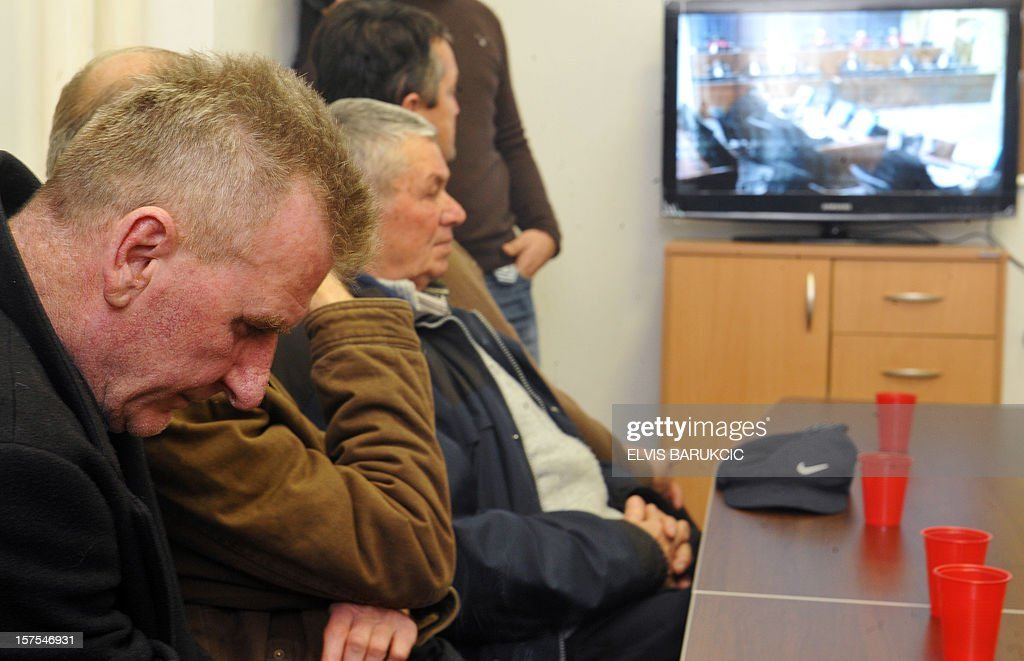 Bosnian Muslim men, Hamdija Vilic (L) and Esad Tufekcic (2nd L), survivors of the 1992 massacres in the Eastern-Bosnian town of Visegrad, gather on December 4, 2012, to watch in Sarajevo a live television broadcast of the final ruling in the trial of two former Bosnian Serb army officers, Sredoje Lukic and Milan Lukic, before the International Criminal Tribunal for the former Yugoslavia (ICTY) in the Hague. The UN's Yugoslav war crimes court on December 4 upheld murder convictions against two Bosnian Serb cousins but ordered one of their sentences reduced on appeal.The two cousins were appealing their 2009 convictions at the International Criminal Tribunal for the former Yugoslavia (ICTY) for killing Muslims during Bosnia's 1992-95 war in ways the court had described as 'the worst acts of inhumanity'.