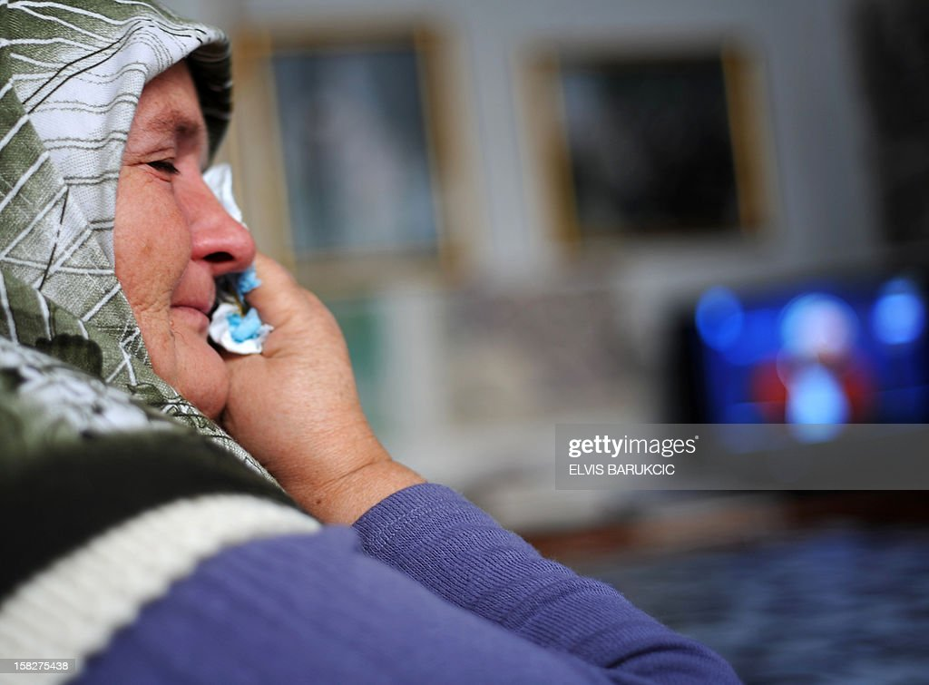 Bosnian Muslim woman, Ramiza Gurdic, survivor of the 1995 massacre in the Eastern-Bosnian town of Srebrenica, cries in Sarajevo on December 12, 2012 as she watches a live television broadcast of the final ruling in the case of former Bosnian Serb general Zdravko Tolimir before the International War Crimes Tribunal for former Yugoslavia (ICTY) in The Hague. The UN's Yugoslav war crimes court found Tolimir guilty of genocide on December 12 for his role in the 1995 Srebrenica massacre, Europe's worst atrocity since World War II, and sentenced him to life in jail.