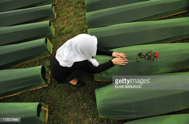 A Bosnian Muslim woman survivor of Srebrenica 1995 massacre mourns over body casket of her relative at memorial cemetery in village of Potocarion...