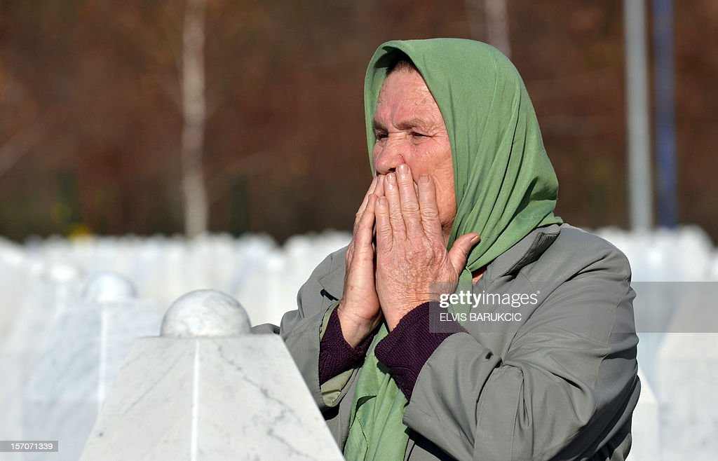 A Bosnian Muslim woman, survivor of the 1995 Srebrenica massacre, mourns at the tomb of a relative at the Memorial cemetery in Potocari, near Eastern-Bosnian town of Srebrenica, on November 28, 2012. AFP PHOTO ELVIS BARUKCIC
