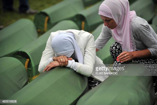 A Bosnian Muslim woman survivor of the Srebrenica 1995 massacre cries by the coffin of a relative layed out among others at the memorial cemetery in...