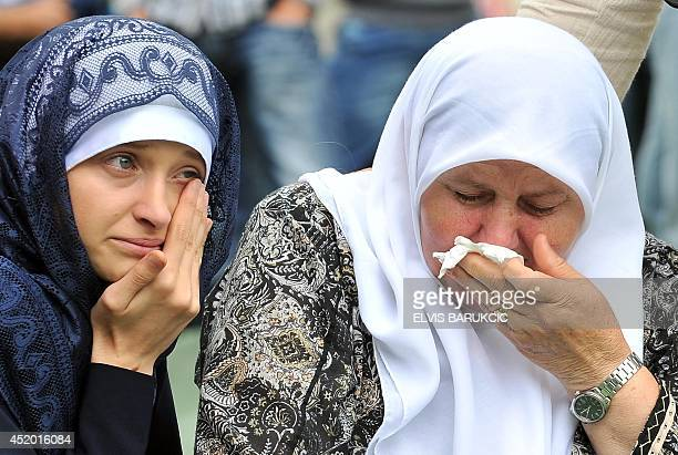 Bosnian Muslim women cry in front of the coffin of a relative layed out among others at the SrebrenicaPotocari Genocide Memorial cemetery in the...