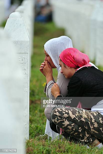 Bosnian Muslim women survivor of Srebrenica 1995 massacre mourn next to the grave of her relative at a memorial cemetery in the village of Potocari...