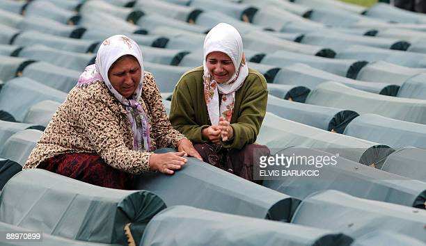 Bosnian Muslim women weep by the coffin of her relative among coffins of Srebrenica victims displayed at the memorial centre of Potocari near...