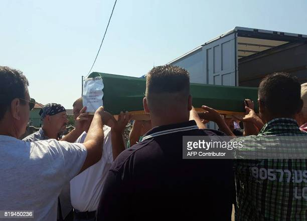 Bosnian muslims survivors of ethnic cleansing in NorthWestern Bosnia in 1992 carry body caskets during mass burrial ceremony in Prijedor on July 20...