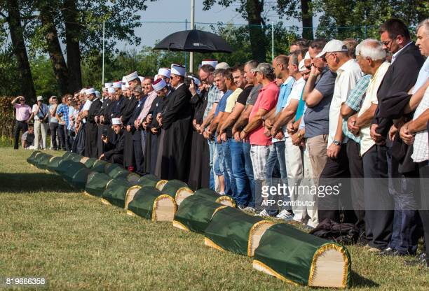 Bosnian Muslims survivors of ethnic cleansing in NorthWestern Bosnia in 1992 pray next to coffins during a mass burial ceremony in Prijedor Bosnia...