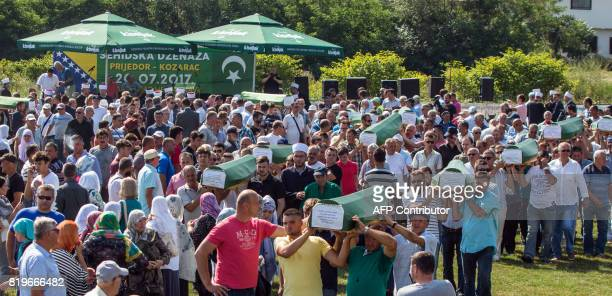 Bosnian Muslims survivors of ethnic cleansing in NorthWestern Bosnia in 1992 carry coffins during a mass burial ceremony in Prijedor Bosnia and...