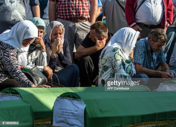 Bosnian Muslims survivors of ethnic cleansing in NorthWestern Bosnia in 1992 react next to coffins during a mass burial ceremony in Prijedor Bosnia...