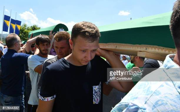 Bosnian Muslims survivors of Srebrenica 1995 massacre as well as other visitors carry one of many caskets containing the remains of their relatives...
