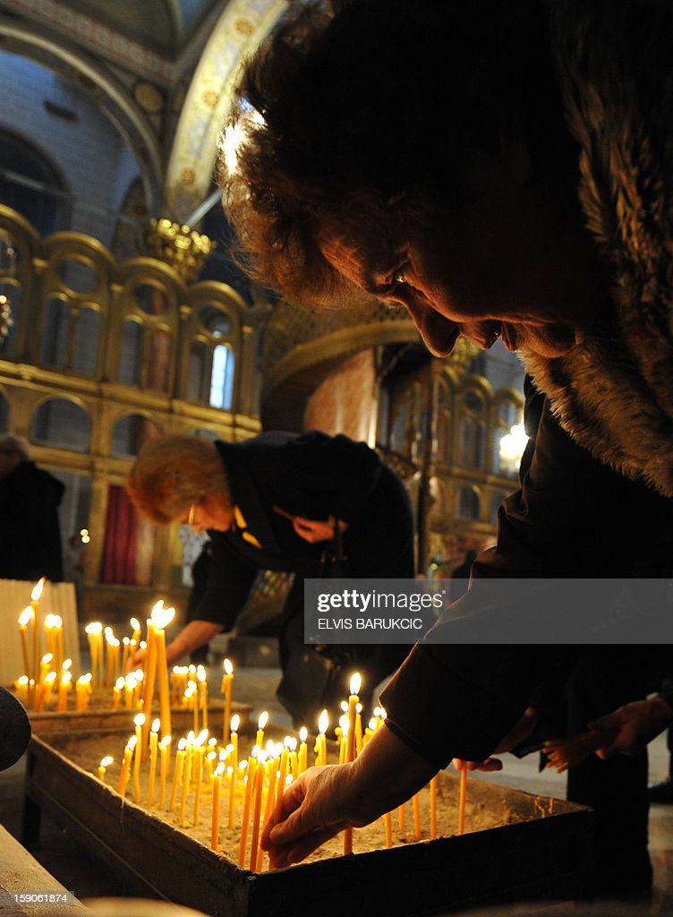 Bosnian Orthodox Serb light candles to commemorate passed souls of their relatives, during Christmas Mass at 'Congregational Church of The Mother of God' in Sarajevo, on January 7, 2013. Dominantly Orthodox Christians, Bosnian Serbs observe the old 'Julian' calendar differing from Catholic and secular, 'Gregorian' calendar, established in 16th century. AFP PHOTO ELVIS BARUKCIC