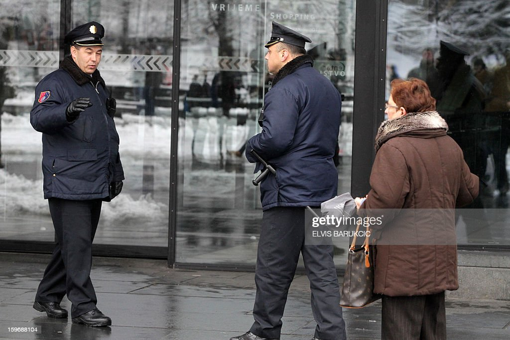 Bosnian police officers secure the entrance to the 'BBI' shopping mall in the business center of Sarajevo, after a bomb threat has been called in, on January 18, 2013. The mall has been evacuated and the police bomb experts have been called to inspect the building.