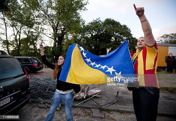 Bosnian residents in the The Netherlands display a Bosnian and Heregovina national flag as they take photographs with a mobile telephone and point to...