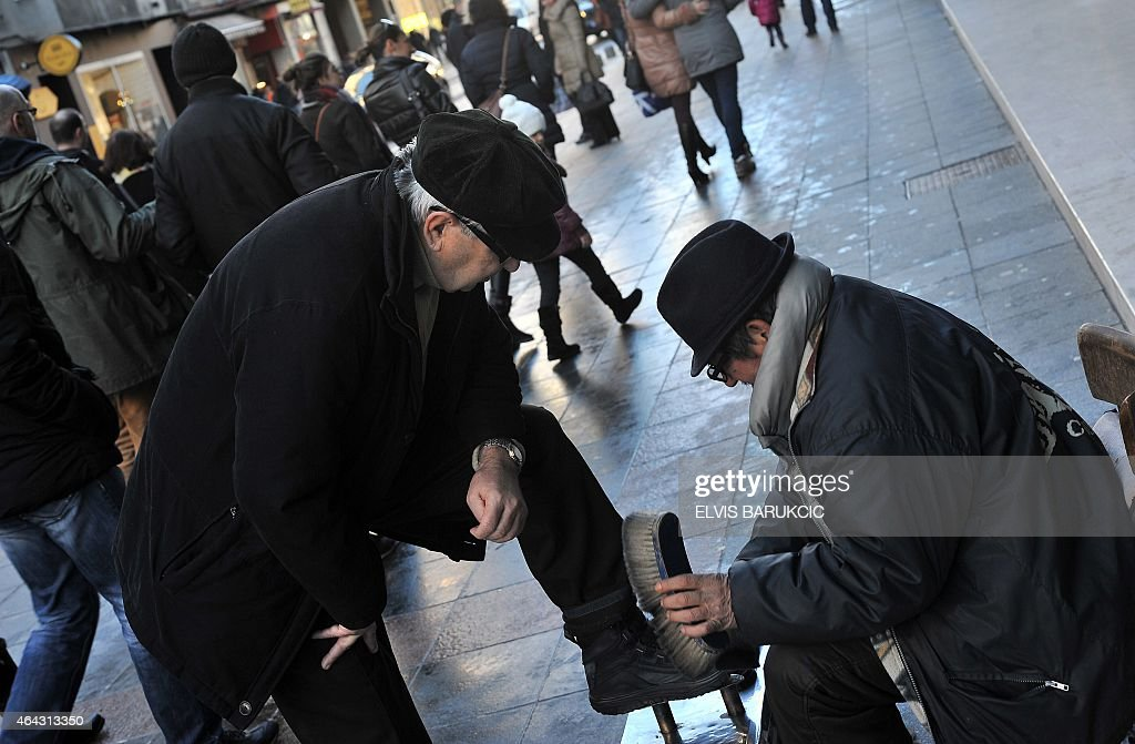 Bosnian Roma man, Ramiz Pasic polishes a shoe at his sidewalk work location, on Sarajevo's main street 'Marshall Tito' on January 31, 2015. Pasic occupies the spot where his late father Husein Hasani used to work for the past 60 years as one of the last shoeshiners in Sarajevo. AFP PHOTO / ELVIS BARUKCIC