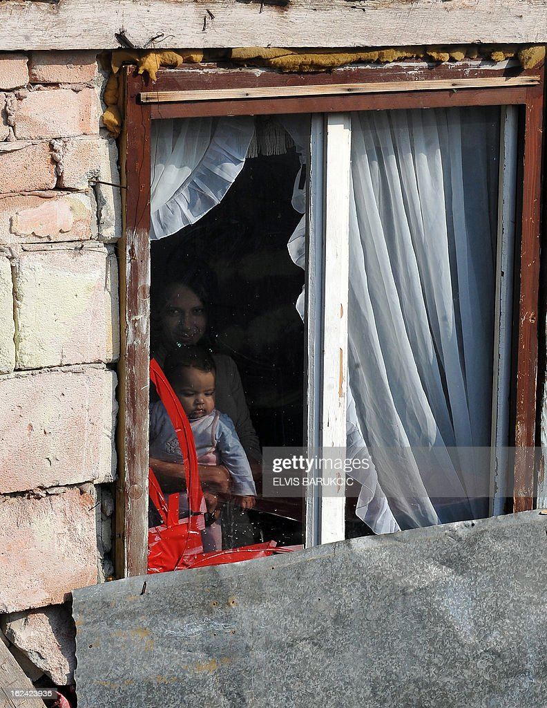 A Bosnian Roma woman and child are seen as they look through a window on their shed in village of Svatovac, on February 20, 2013. Svatovac, an isolated hamlet with some 200 inhabitants near the northern town of Tuzla, is Nazif Mujic's home. Mujic picked up the Silver Bear for best actor at the Berlin Film Festival for his performance in Bosnian director Danis Tanovic's 'An Episode in the Life of an Iron Picker'.