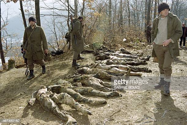 Bosnian Serbs stand near the bodies of the 24 mutilated men discovered in a mass grave they say were killed by Bosnian Moslems in Eastern Bosnian...