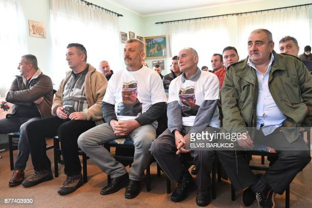 TOPSHOT Bosnian Serbs two wearing a Tshirt showing a portrait of Ratko Mladic watch a live TV broadcast from the International Criminal Tribunal for...
