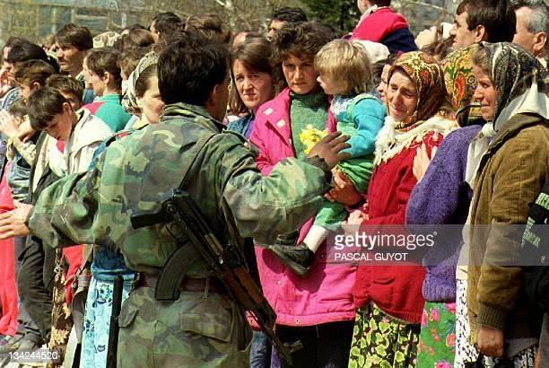 A Bosnian soldier restrains Moslem refugees from Srebrenica who were trying to find their family members in Tuzla 14 April 1993 in BosniaHercegovina...
