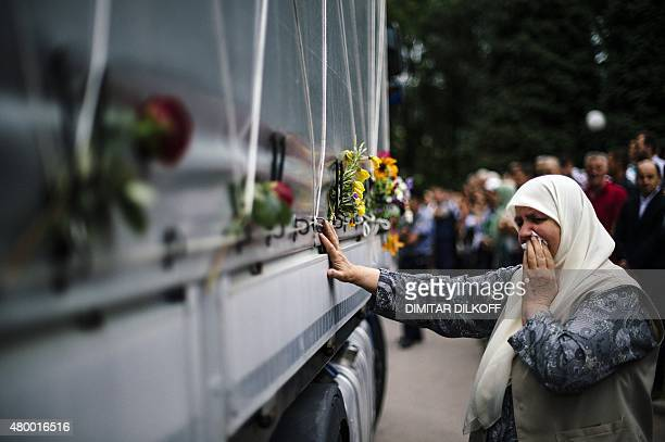 A Bosnian woman cries as she touches a truck carrying 136 coffins of newly identified victims of the 1995 Srebrenica massacre in the town of Visoko...