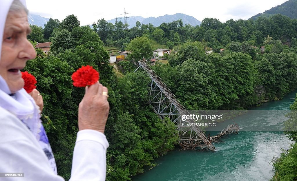 A Bosnian woman throws red carnations, into the river Neretva, in the Southern-Bosnian town of Jablanica, on May 11, 2013. A crowd of several thousand socialist supporters and sympathisers gathered in Jablanica to commemorate the 70th anniversary of The Battle on the river Neretva, one of the most famous battles of World War II in Yugoslavia. The battle was fought by Tito's Partisans who were vastly outnumbered and outgunned by German forces and their domestic helpers. The Partisans carried a large number of wounded fighters and were followed by several thousands of civillians who were fleeing in front of a German offensive.