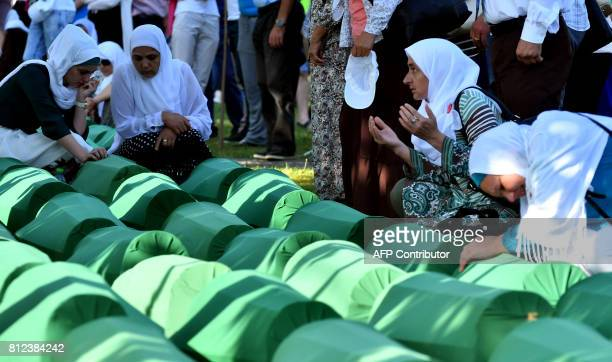 Bosnian women offers prayers near the caskets of 71 victims of the 1995 Srebrenica massacre at the memorial cemetery in the village of Potocari near...