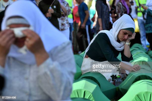 TOPSHOT Bosnian women offers prayers near the caskets of 71 victims of the 1995 Srebrenica massacre at the memorial cemetery in the village of...