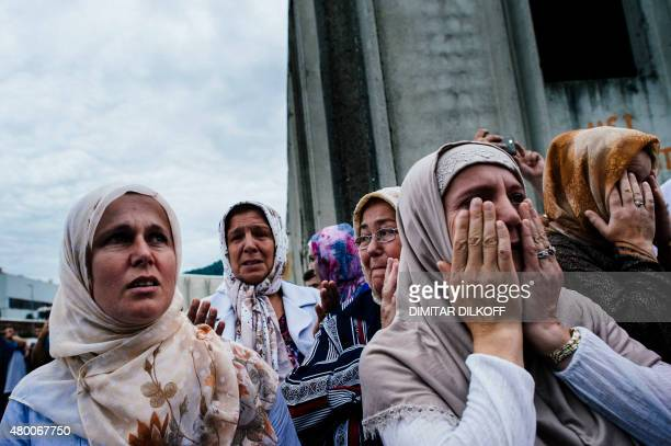 Bosnian women pray when a truck carrying 136 coffins of newly identified victims of the 1995 Srebrenica massacre just arrived at the former battery...