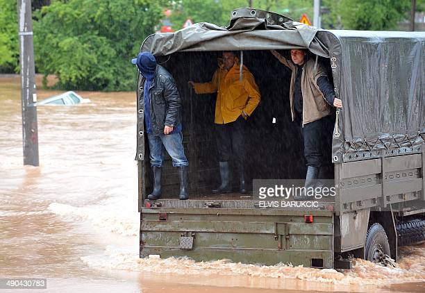 Bosnian workers stand in a military truck while being rescued by the armed forces in Sarajevo's western suburb of Rajlovac on May 14 after being cut...