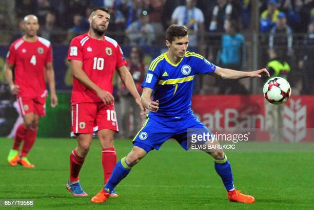 Bosnia's Gojko CImirot steels ball in front of Gibraltar's Liam Walker during the FIFA World Cup 2018 qualification football match between Bosnia and...
