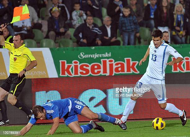 Bosnia's Mensur Mujdza fouls Greece's Avraam Papadopoulos during a friendly football match between the two national teams in Sarajevo on August 10...