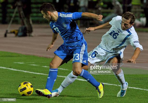Bosnia's Senad Lulic attempts to get the ball away from Greece's Ioannis Fetfatzidis during their international friendly football match in Sarajevo...