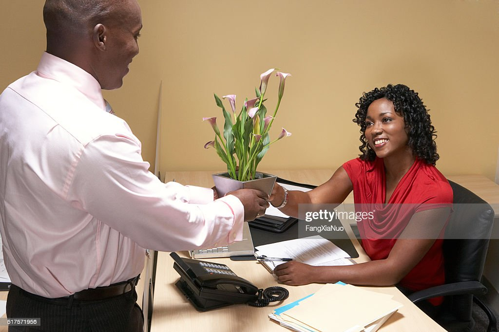 Boss giving his administrative assistant flowers : Stock-Foto