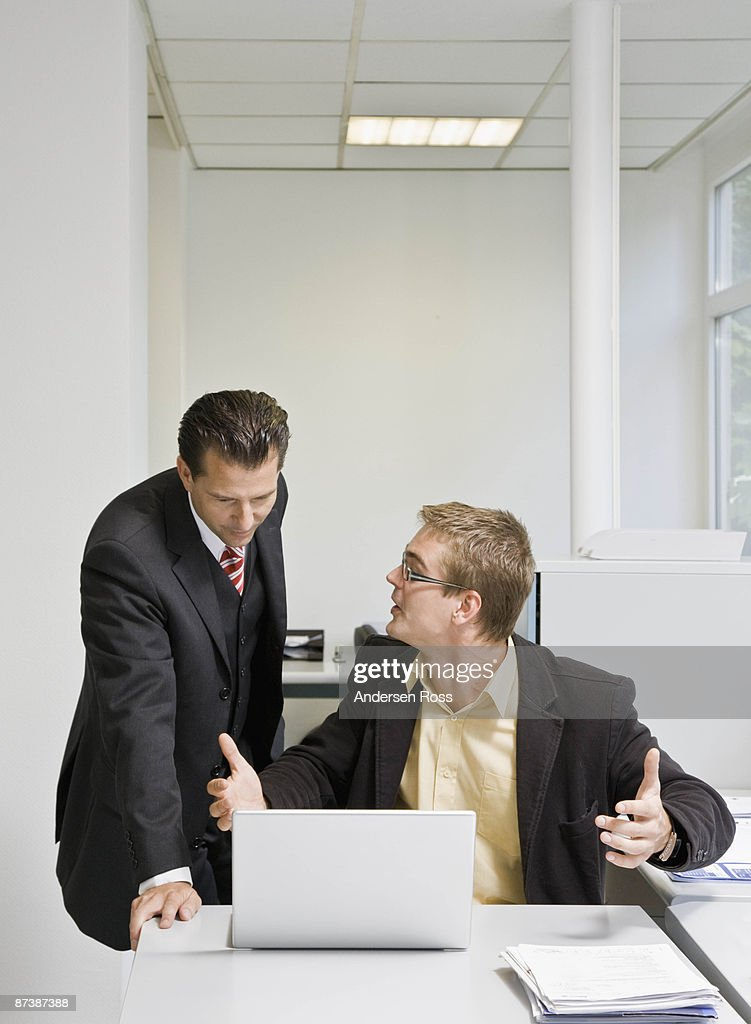 Boss looking at laptop with co-worker : Stock Photo