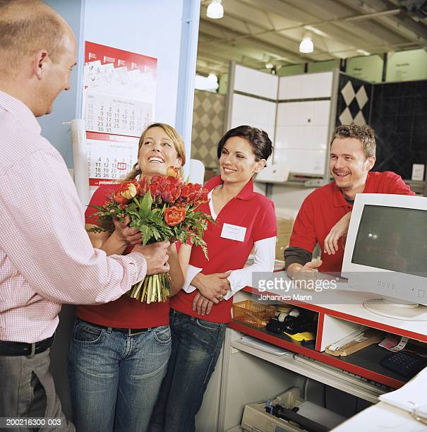 Boss presenting bunch of flowers to employee, colleagues watching