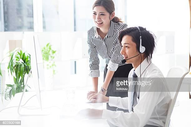 Boss teaching businessmen at call center