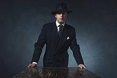 Bossy vintage 1940 businessman standing behind wooden table.