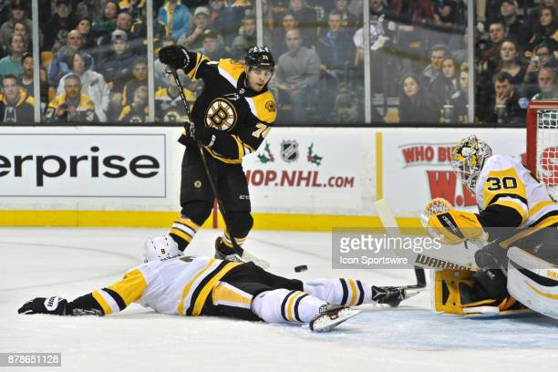 Boston Boston Bruins Left Wing Jake Debrusk passes the puck over Pittsburgh Penguins Defenceman Brian Dumoulin During the Boston Bruins game against...