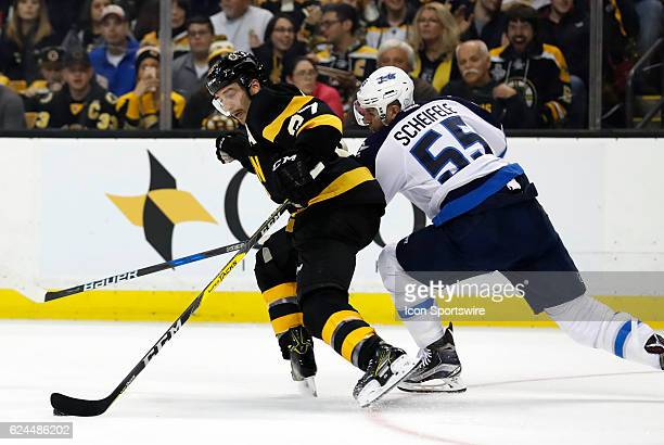 Boston Bruins center Patrice Bergeron uses his body to keep Winnipeg Jets center Mark Scheifele from the puck during a regular season NHL game...