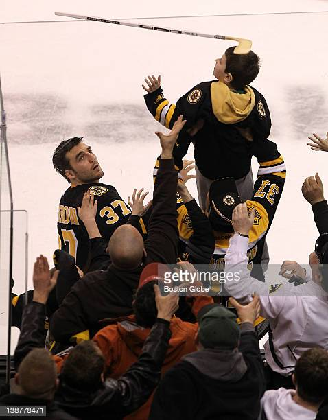 Boston Bruins center Patrice Bergeron who was named the number one star of the game flips his stick to a lucky fan Boston Bruins took on the...
