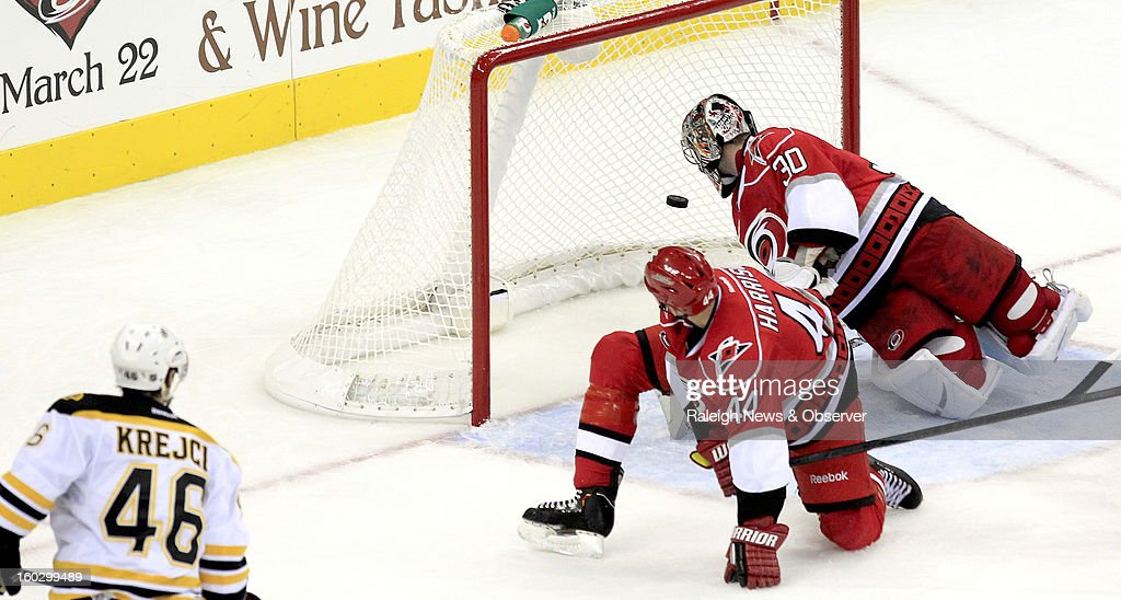 Boston Bruins' David Krejci (46) scores a go-ahead goal past Carolina Hurricanes Jay Harrison (44) and Cam Ward (30) during the third period at PNC Arena in Raleigh, North Carolina, Monday, January 28, 2013. The Bruins beat the Hurricanes 5-3.