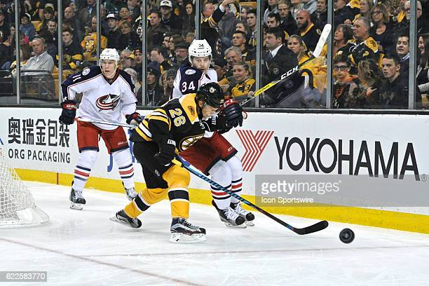 Boston Bruins Defenceman JohnMichael Liles separates Columbus Blue Jackets Right Wing Josh Anderson from the puck behind the net During the Boston...