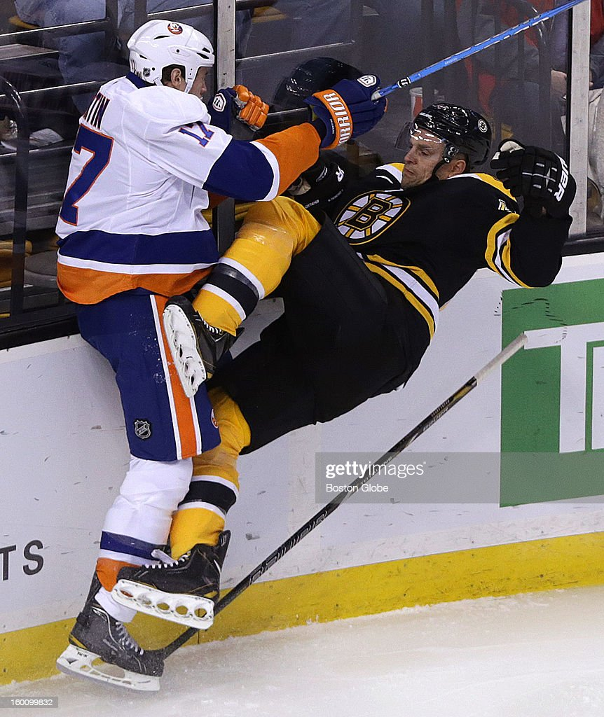 Boston Bruins defenseman Dennis Seidenberg (#44) takes a big hit from New York Islanders left wing Matt Martin (#17) along the boards in the first period as the Boston Bruins play the New York Islanders in an NHL regular season game at TD Garden.