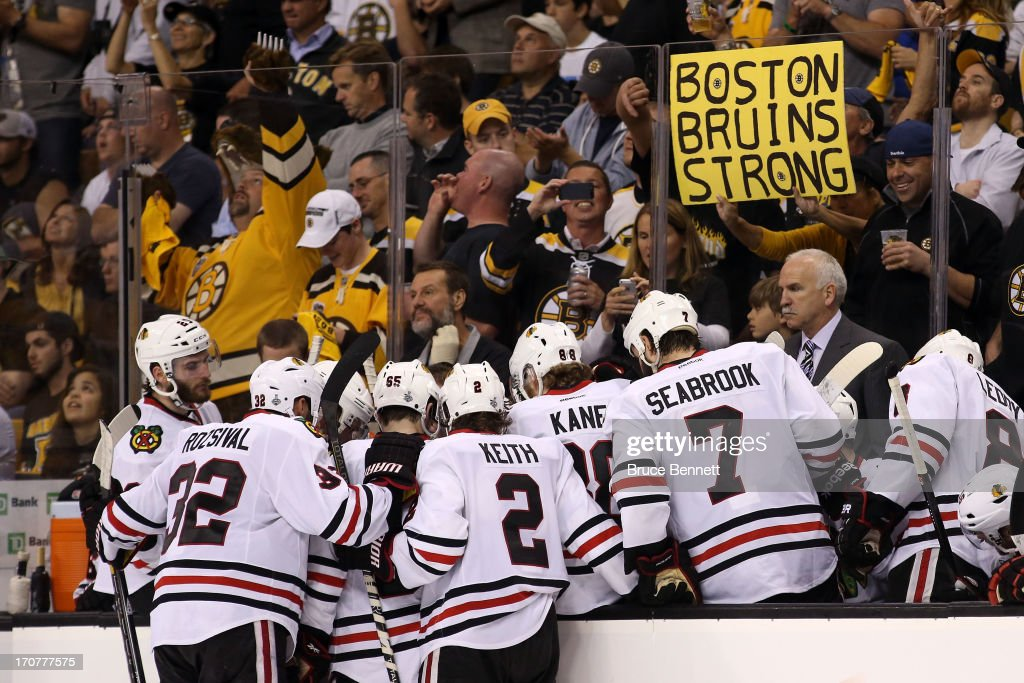 A Boston Bruins fan holds a 'Boston Bruins Strong' sign behind head coach <a gi-track='captionPersonalityLinkClicked' href=/galleries/search?phrase=Joel+Quenneville&family=editorial&specificpeople=2094832 ng-click='$event.stopPropagation()'>Joel Quenneville</a> of the Chicago Blackhawks and his team in Game Three of the 2013 NHL Stanley Cup Final at TD Garden on June 17, 2013 in Boston, Massachusetts.