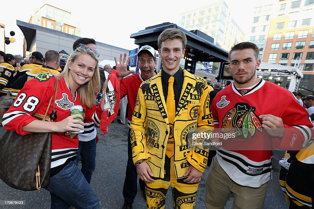 A Boston Bruins fan wearing a suit of rally towels poses with Chicago Blackhawks fans before Game Four of the 2013 Stanley Cup Final between the Chicago Blackhawks and the Boston Bruins at TD Garden on June 19, 2013 in Boston, Massachusetts.