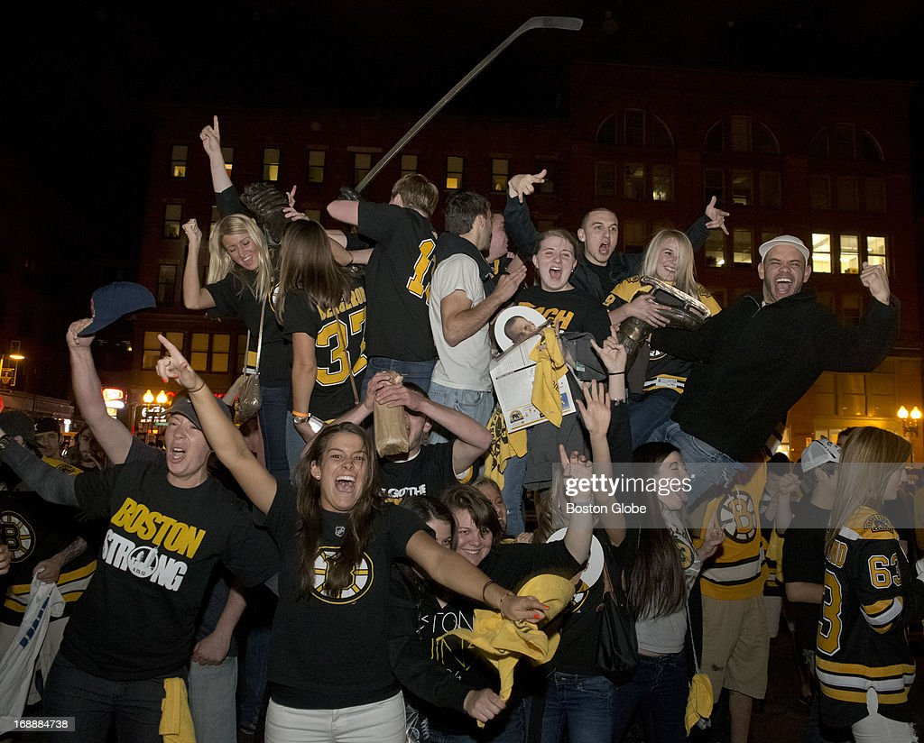 Boston Bruins fans, hanging off of the Bobby Orr statue outside of the TD Garden, celebrate the Bruins' 5-4 sudden death victory over the Toronto Maple Leafs during Game Seven of the Eastern Conference quarterfinals on Monday, May 13, 2013.