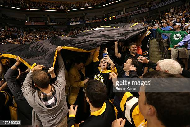 Boston Bruins fans pass the Bruins banner hand to hand at the start of Game Three The Boston Bruins hosted the Chicago Blackhawks for Game Three of...