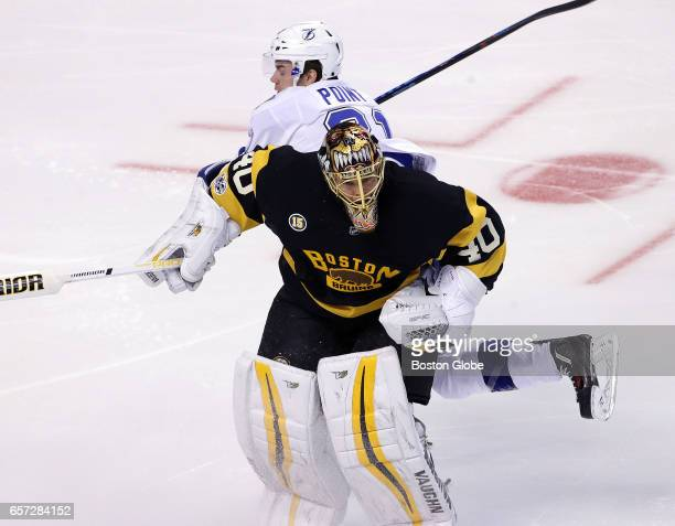 Boston Bruins goalie Tuukka Rask comes way out of his crease to knock the puck away from Tampa Bay Lightning center Brayden Point applying a hip...