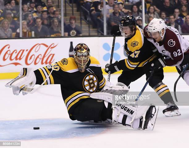 Boston Bruins goalie Tuukka Rask falls back on the puck to save a goal with help from teammate defenseman Torey Krug as they are pressured by...