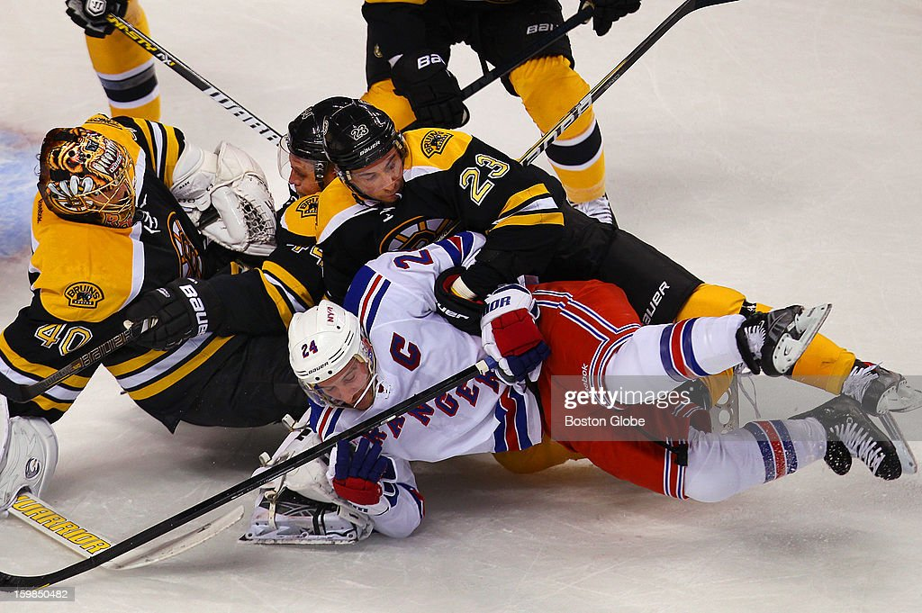 Boston Bruins goalie Tuukka Rask gets piled on in the first period as the Bruins' Chris Kelly checks Rangers player Ryan Callahan off the puck in front of the net during the season opener, in which the Boston Bruins hosted the New York Rangers in an NHL regular season game at the TD Garden.