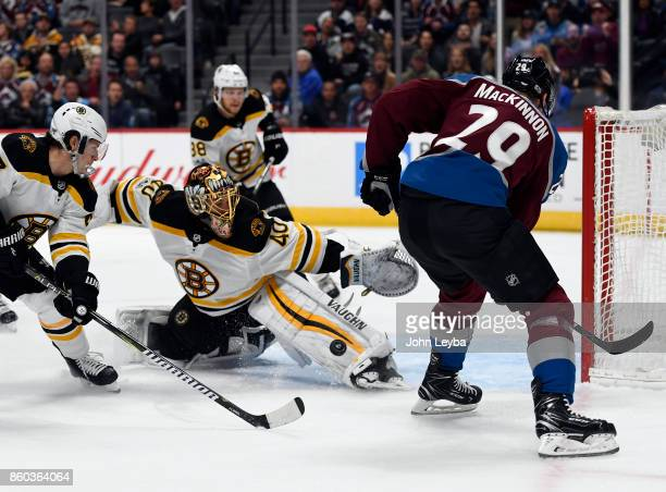Boston Bruins goalie Tuukka Rask makes a save on a bouncing puck as Colorado Avalanche center Nathan MacKinnon looks on during the first period...