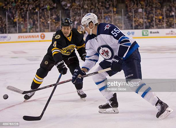 Boston Bruins Gregory Campbell battles Winnipeg Jets Mark Scheifele for control of the puck during first period action at the TD Garden on Saturday...